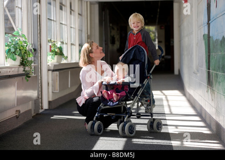 Mother with young son and baby in a stroller in the hallway of an elementary school. - Stock Photo