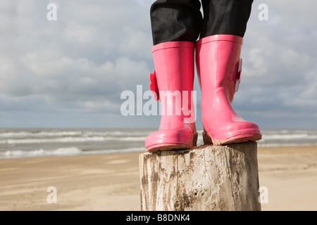 Child standing on a pole in boots - Stock Photo