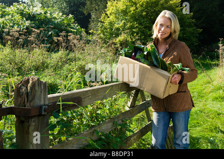 Woman holding box of vegetables - Stock Photo