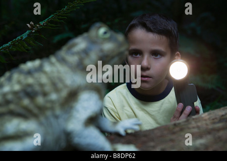 Boy with torch and toad - Stock Photo