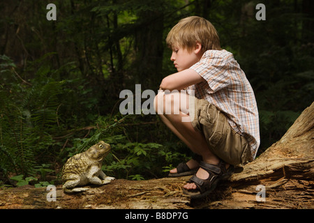 Boy looking at toad - Stock Photo