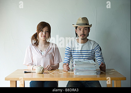 Young couple with string and magazines - Stock Photo