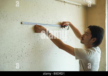 Young man measuring wall - Stock Photo