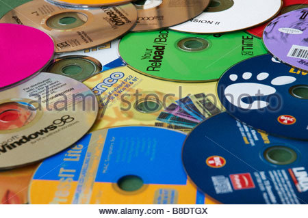 Excessive amount of computer software information and programs on cd's dvd's compact discs - Stock Photo