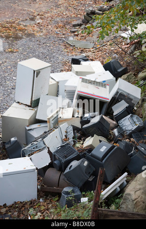 Britain UK Pile of domestic electrical appliances dumped outside. Fridges freezers and televisions - Stock Photo