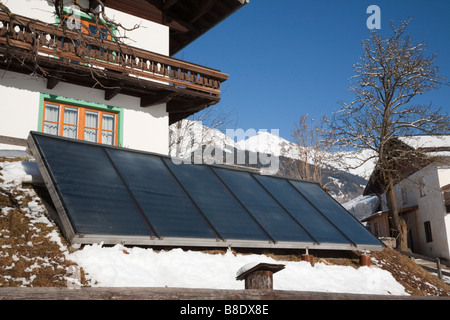 Austria Europe. Large solar panels outside an Austrian chalet house for domestic home water heating - Stock Photo