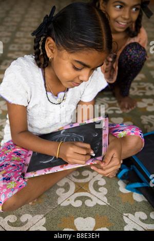 Schoolgirl working on a small blackboard, doing her homework. Hazira, Surat, Gujarat. India - Stock Photo