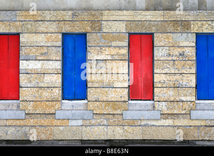 Four closed metal window shutters over stone covered wall. - Stock Photo