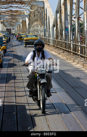 Foreign Tourist Riding a Motorcycle Across the Faidherbe Bridge in St Louis in Senegal Africa - Stock Photo