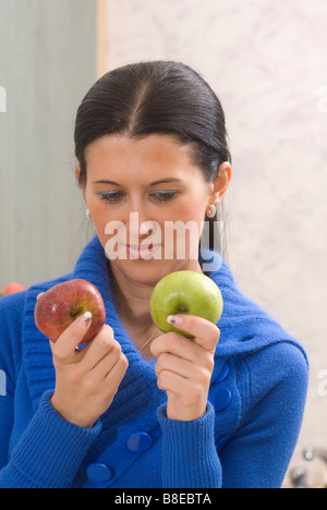 Woman choosing between green and red apples - Stock Photo