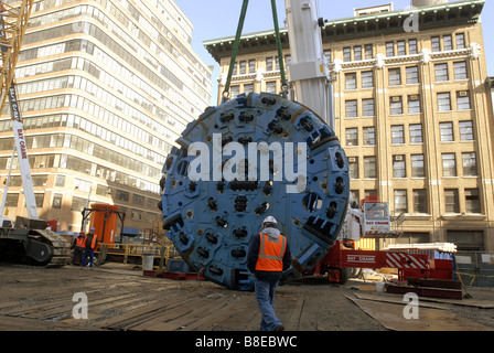 Construction workers prepare to lower the 100 ton cutting head of a tunnel boring machine down a shaft into an assembly - Stock Photo