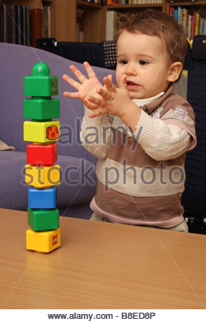 A toddler boy of 18 months old playing with building bricks. - Stock Photo