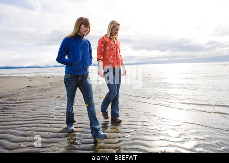 Two young women walk along Bishop's Beach in Homer, Alaska - Stock Photo