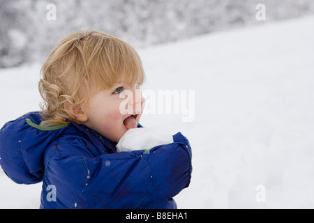 Young boy licking a snowball on a winter walk in Pedro Bay, Alaska - Stock Photo