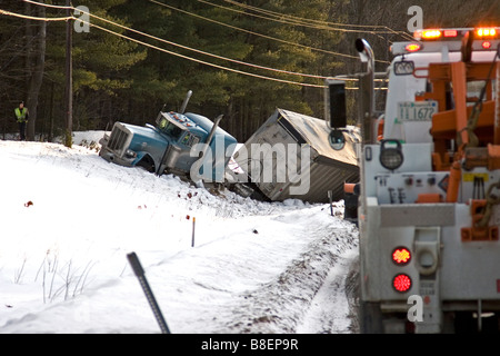 A tow truck arrives at the scene of a lorry accident. - Stock Photo