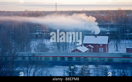 Aerial view of passenger train passing a wooden detached house at very cold Winter morning , Oulu  Finland - Stock Photo