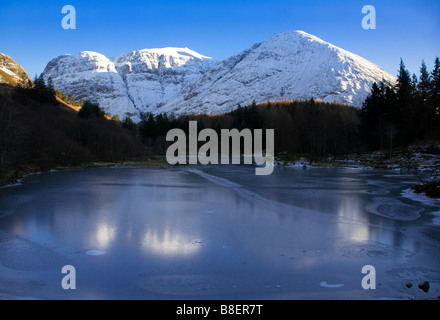 A snow covered Bidean nam Bian and frozen Lochan in Winter, Glen Coe, Lochaber, Scotland. - Stock Photo