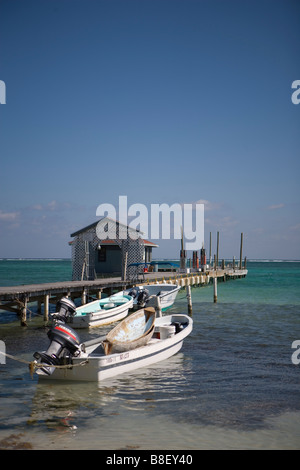 A small boat piggy-backs on top of another larger boat in the shallows in front of a wooden pier near SanPedro on - Stock Photo