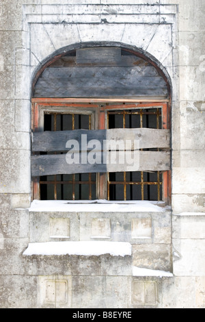 Old building window frame blocked up with wooden boards. - Stock Photo