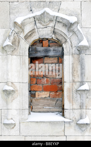Old building window frame piled up with bricks. - Stock Photo