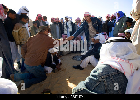 Two bedouin officials shake hands on agreement to the rules and regulations of the annual camel race in Egypt - Stock Photo