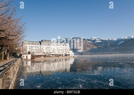 Frozen Zeller See lake and lakeside Grand Hotel in alpine resort in winter. Zell am See Austria Europe - Stock Photo
