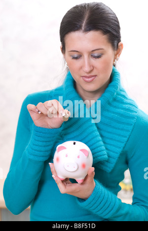 Woman saving money in piggy bank - Stock Photo