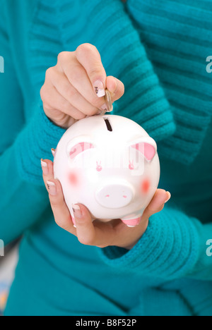 Woman saving money in piggy bank - Stock Photo
