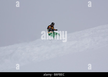 Young Snowboarder wearing green pants and coloured jacket riding through the lovely soft powder in the French resort - Stock Photo