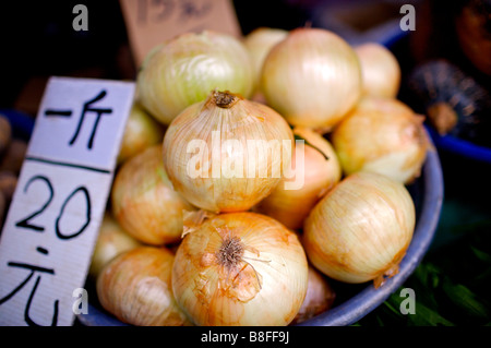 Onions on display on a plastic tray with the price written on a piece of cardboard - Stock Photo