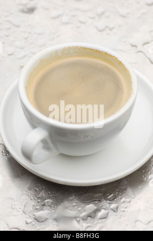 Close up of a cup of coffee outdoors on a wet surface - Stock Photo