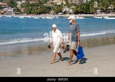 senior couple briskly walking barefoot along the sand at the edge of Puerto Escondido harbor harbour, Oaxaca, Mexico