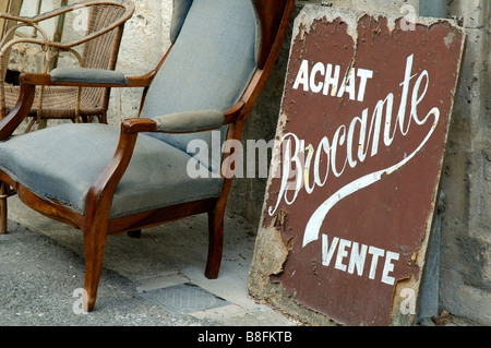 Old weathered antiques sign and chair outside a bric-a-brac shop, Burgundy, France. - Stock Photo