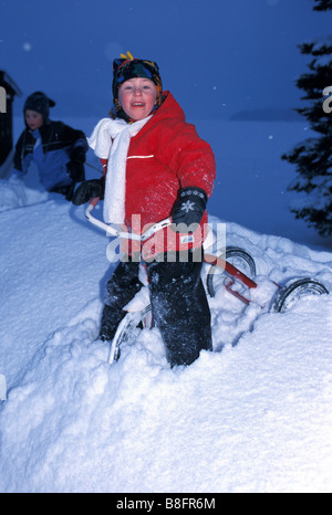 Girl rides tricycle in the snow in northern ontario - Stock Photo
