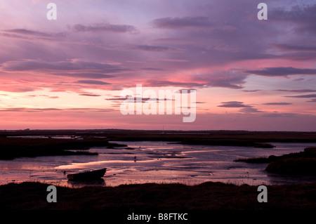 Sunset over a boat on saltmarsh in Burnham Deepdale, North Norfolk, England, UK - Stock Photo