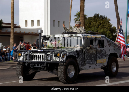 US Army in the Fiesta Bowl Parade with a camouflaged hummer.  A U.S. flag is off the backside and a soldier is waving - Stock Photo