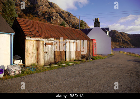 Corrugated iron Storage sheds, telephone kiosk, and main street. Lower Diabaig, Wester Ross, Scotland - Stock Photo