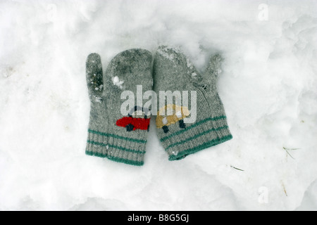 Pair of kid's gloves lying in the snow - Stock Photo