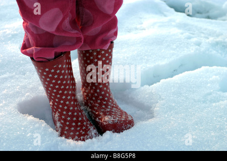 Girl standing in the snow - Stock Photo