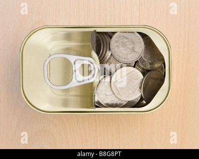 Ring Pull Tin Can Containing Ten Pence Pieces on a Wooden Surface - Stock Photo