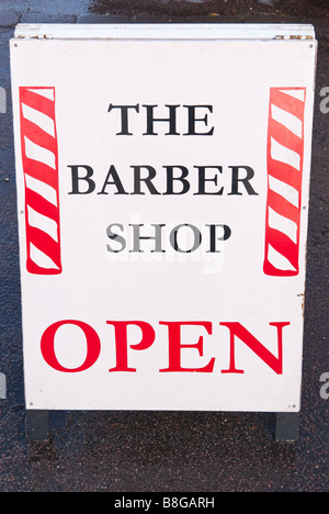 The barber shop open sign outside a uk barbers shop salon - Stock Photo
