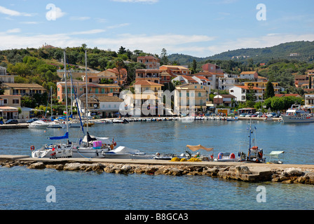 Kassiopi harbour, Corfu, with various boats tied to jetty and to harbour wall - Stock Photo
