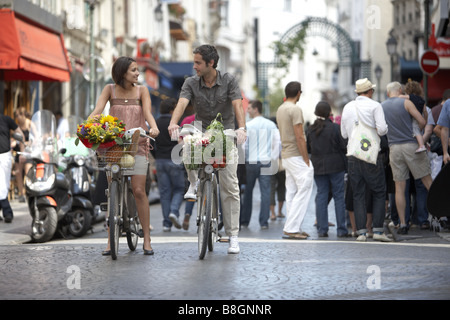 Young couple biking on the Velib® in Central Paris, France. - Stock Photo