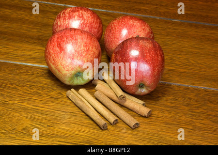 Red apples and cinnamon sticks on a wooden table - Stock Photo