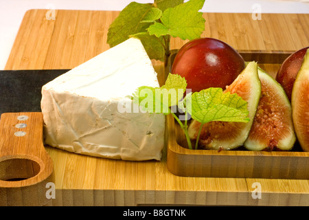 Cheese and fruits on a cheese board - Stock Photo