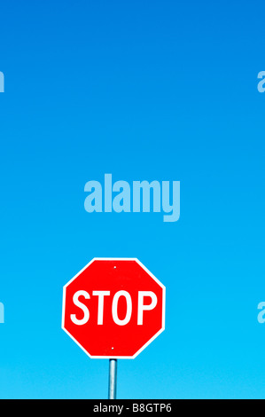 Stop sign red and white against clear deep blue sky - Stock Photo