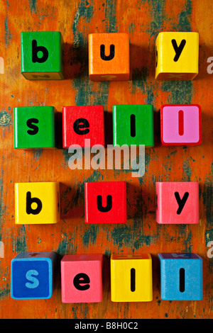 Childrens blocks spelling out buy sell - Stock Photo