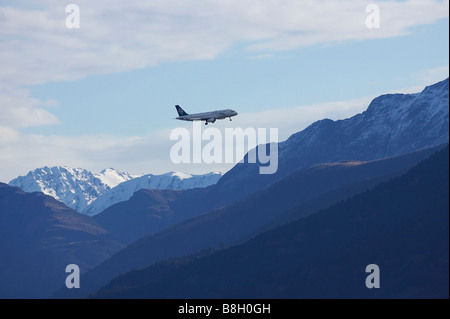 Air New Zealand Jet over Snowy Mountains near Queenstown South Island New Zealand - Stock Photo