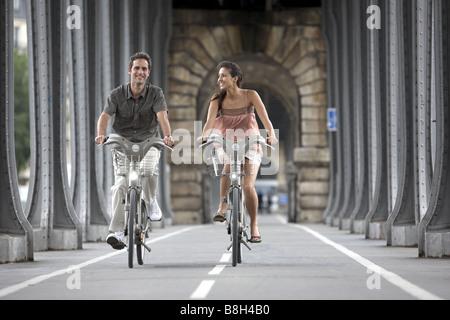 Young couple on Velib® bikes on Paris, France. - Stock Photo