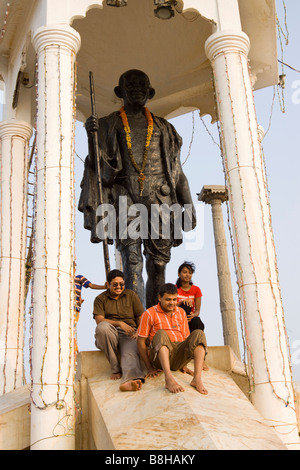 India Pondicherry Indian tourists posing on seafront statue of Gandhi - Stock Photo